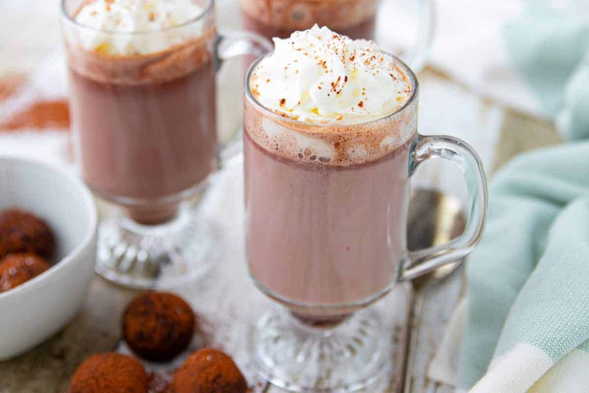 three clear glasses with hot chocolate with whipped cream with hot chocoalte bombs next to them.