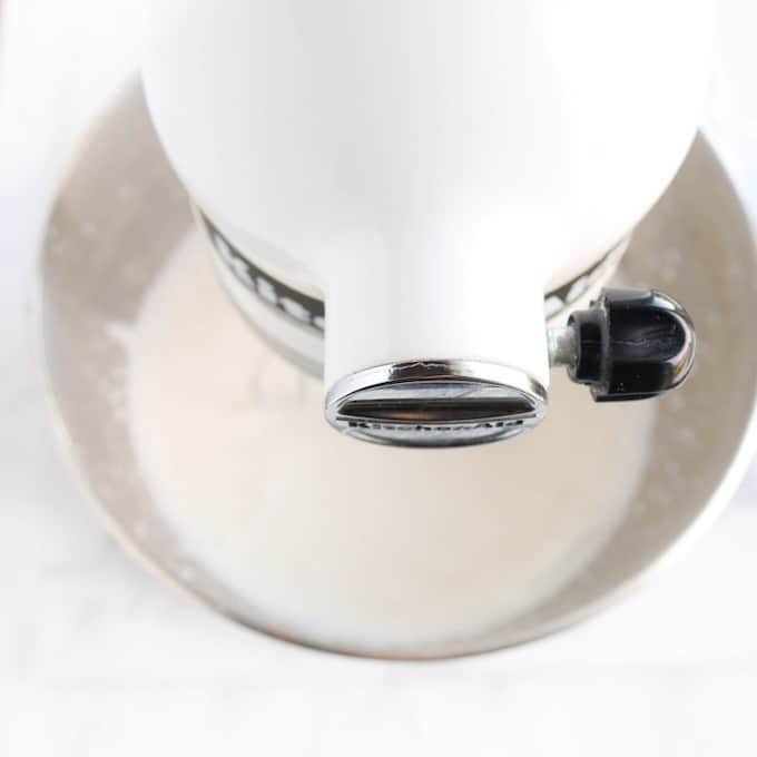 Stabilized Whipping Cream being made, showing a top down photo of a white kitchen-aid mixer whisking whipping cream in its metal bowl.
