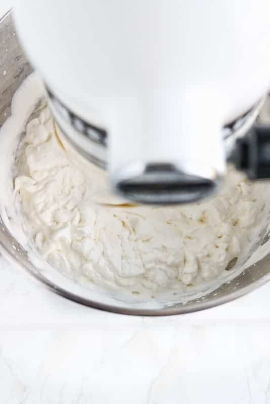 Stabilized whipped cream shown from top down view of a white kitchen aid mixer showing soft to medium peaked whipped cream in a metal mixing bowl.