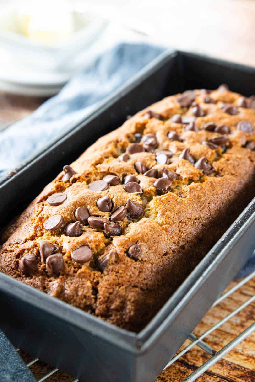 A freshly baked loaf of chocolate chip banana bread shown up close in a bread pan on a cooling rack.