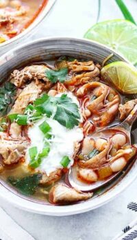 A bowl of chicken chili shown in a bowl with white beans, chicken celery and some sour cream and fresh green onions on top.