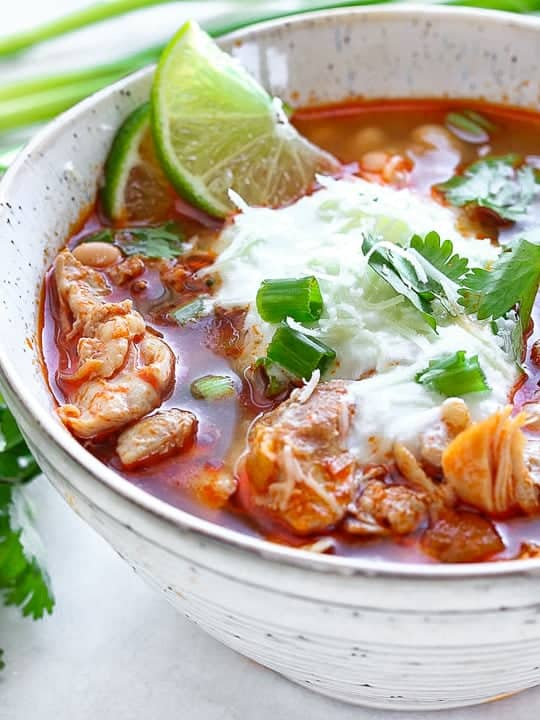 Southwest Chicken Chili shown up close with sour cream, cilantro and lime in a white bowl.