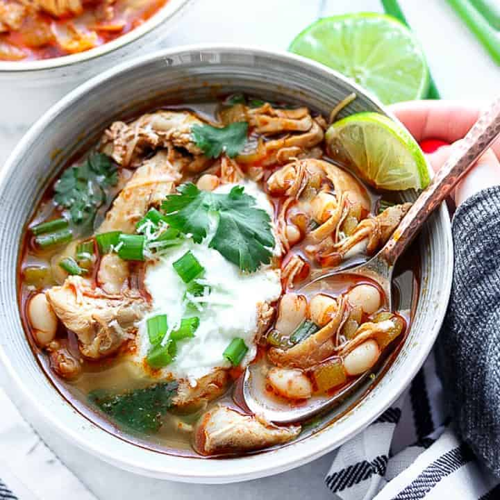 Southwest chicken chili shown in a gray bowl with chicken, beans, Greek Yogurt, and cilantro on a white surface with a hand next to the bowl and spoon.