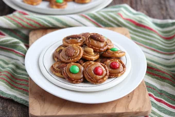 Christmas Pretzel treats shown on a white plate with a green and red stripped kitchen towel underneath all on a wooden surface.