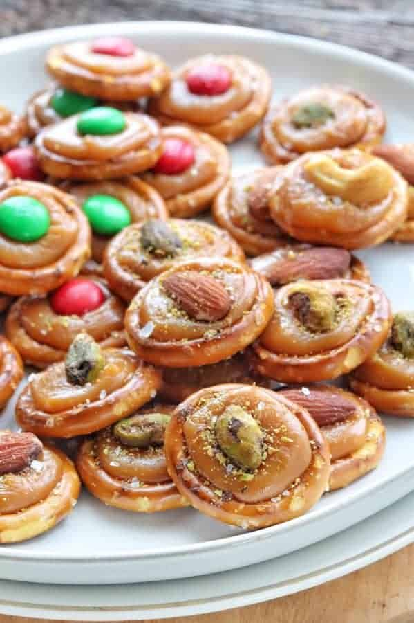 Christmas Pretzels shown with M&M's and pistachios in caramel on a white plate.