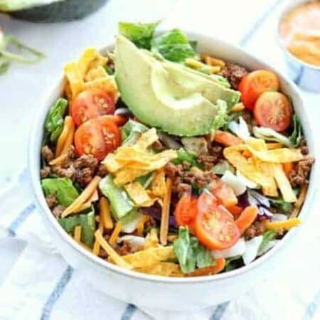 Taco salad shown in a blow with fresh tomatoes and avocado on top.