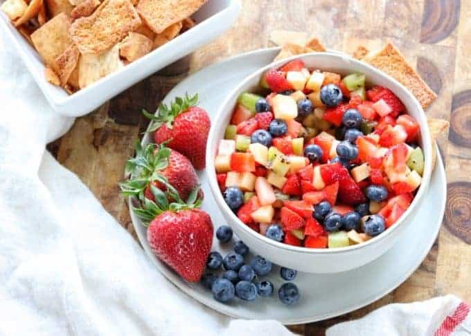 Fruit salsa in a serving bowl next to a bowl of cinnamon and sugar pita chips.