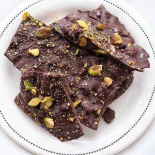 Dark chocolate pistachio bark shown on a white plate.