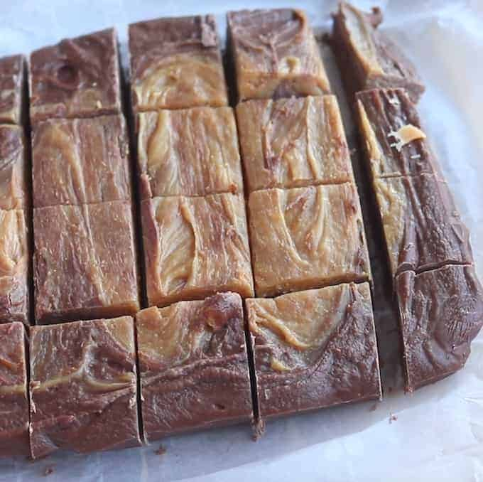 Easy Peanut butter fudge shown cut into squares on a white surface.