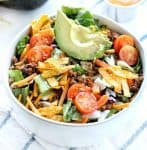 Healthy taco salad recipe shown in a white bowl with fresh tomatoes and avocados on top with tortilla crisps all on a white surface.