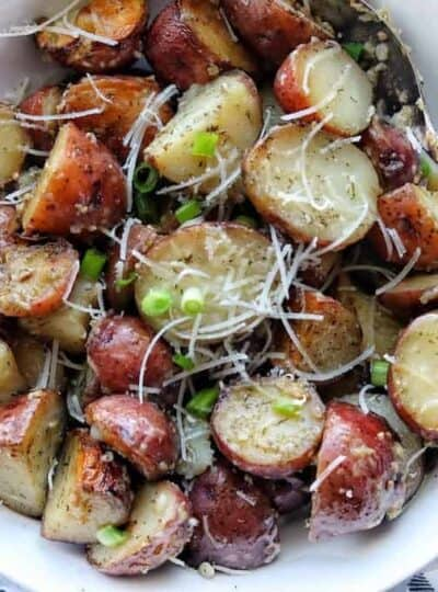 A white bowl with roasted red potatoes sliced in half with shredded parmesan and green onion on top.