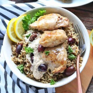 A white bowl with rice and chicken thigh with a creamy sauce and kalamata olives.