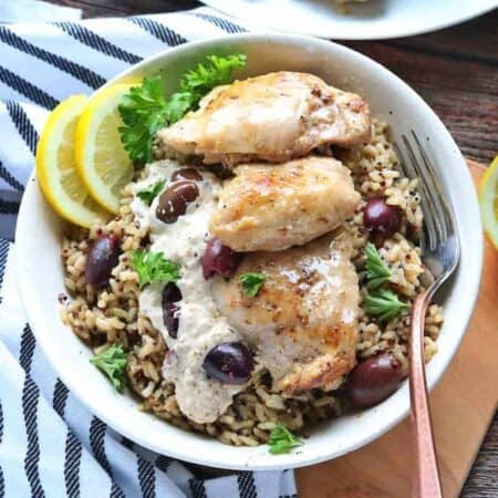 chicken thighs on top of wild rice with a cream sauce