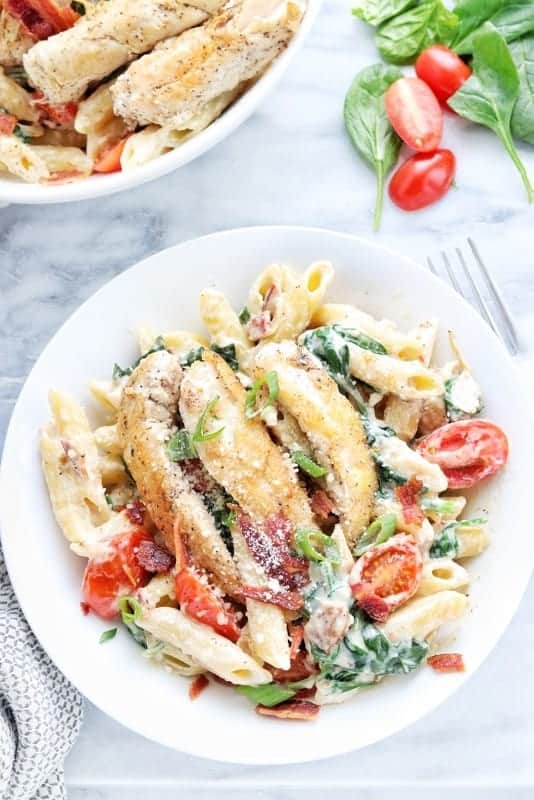 Creamy Chicken and Bacon Pasta recipe shown served in a white bowl with creamy pasta on the bottom and chicken tenders on the top. There is another bowl in the background with spinach and tomatoes next to it on a white marble surface.