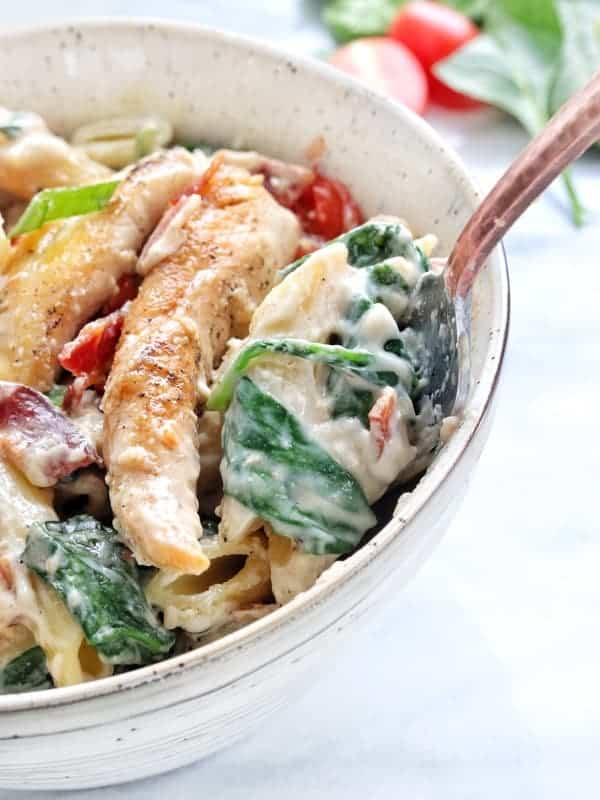 Creamy Chicken and Bacon Pasta recipe shown up close in a white bowl with a fork on a white marble surface. The Creamy chicken pasta has spinach and tomatoes with parmesan cheese and bacon on top.