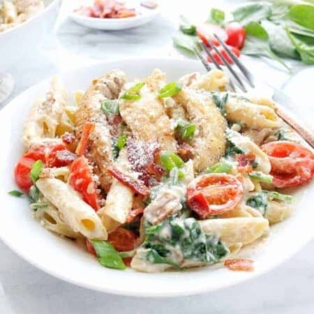 A white bowl with creamy chicken pasta with bacon, tomatoes, and spinach.