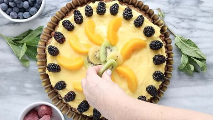 Fruit flan, a healthy dessert idea shown with blackberries, peaches, and kiwi added to the top. The flan is in the middle surrounded by small white bowls of blueberries & strawberries on a white marble surface.