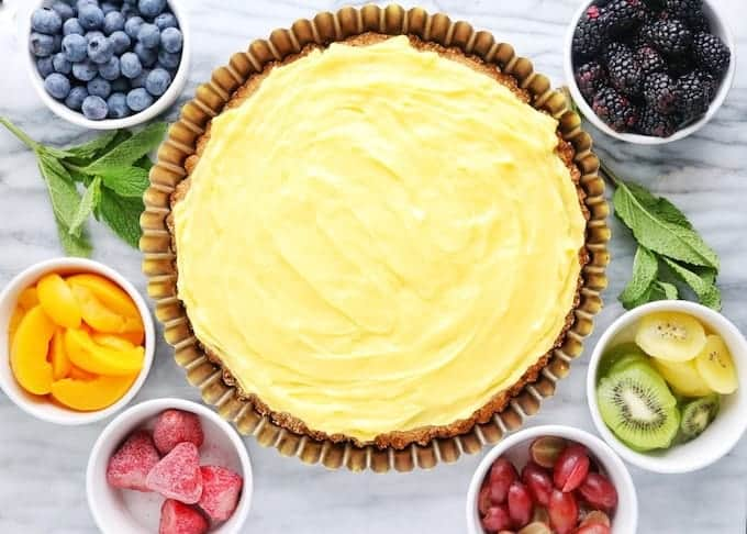 Fruit flan, a healthy dessert idea shown before fruit is on the custard. The flan is in the middle surrounded by small white bowls of blueberries, blackberries, peaches, strawberries, and kiwi on a white marble surface.