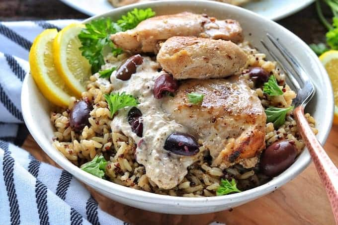 A Greek chicken thigh recipe shown up close in a white bowl with olives, cream sauce, and chicken thighs on top of rice with lemon slices and parsley on a wooden board with a striped kitchen towel.