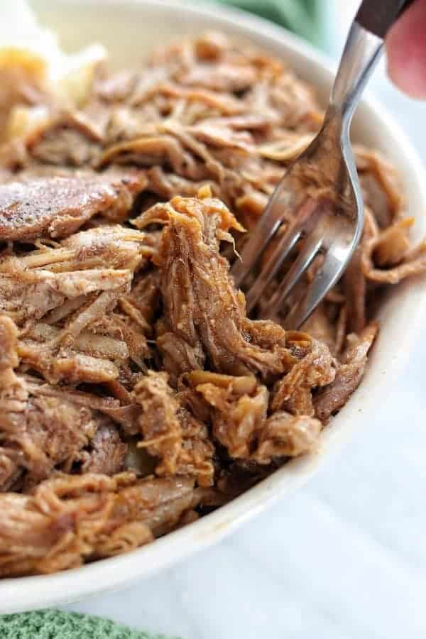 pulled pork in a white bowl with a fork dipping into the bowl on top of a white surface.