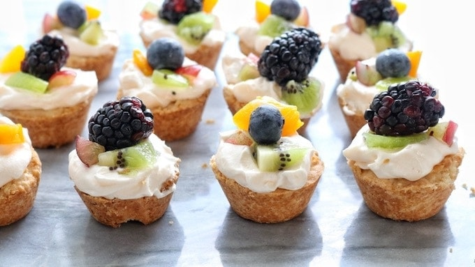 Mini Tarts recipe shown on a white marble surface lined up in 4 rows each mini fruit tart has a shortbread crust, whipped topping, and kiwi, peaches, blackberries, and blueberries.