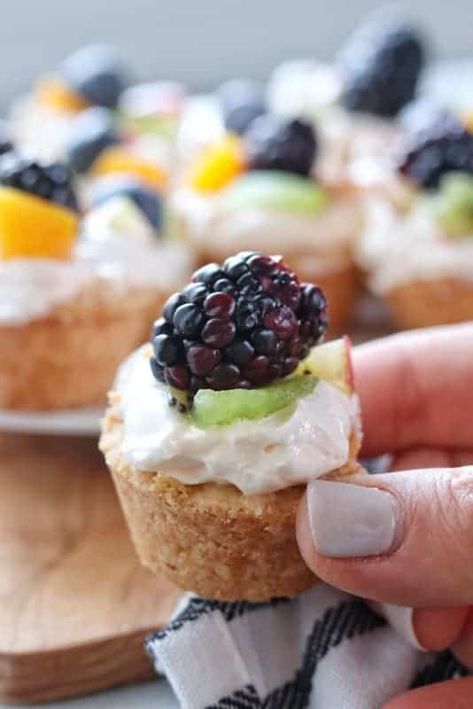 Mini Tarts recipe shown close up mini fruit tart has a shortbread crust, whipped topping, and kiwi, peaches, blackberries with the rest of the tarts in the background blurred.