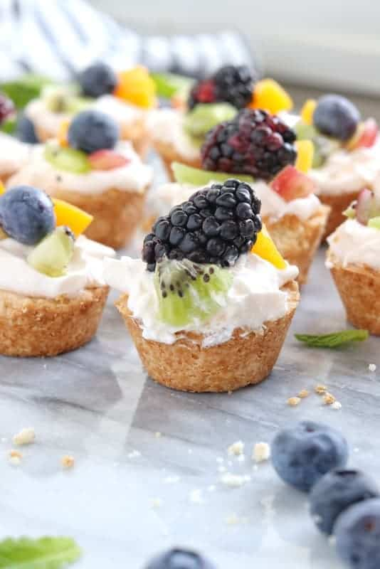 Mini Tart recipe shown complete with a fresh blackberry on the mini fruit tart shown close up with the rest of the tarts in the background