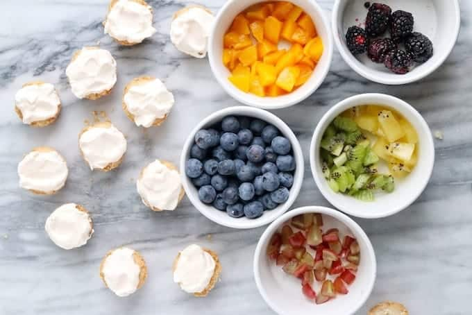 Mini tarts being assembled showing the whipped topped fruit tarts on a white marble surface next to white bowls containing diced peaches, blueberries, kiwi, and blackberries