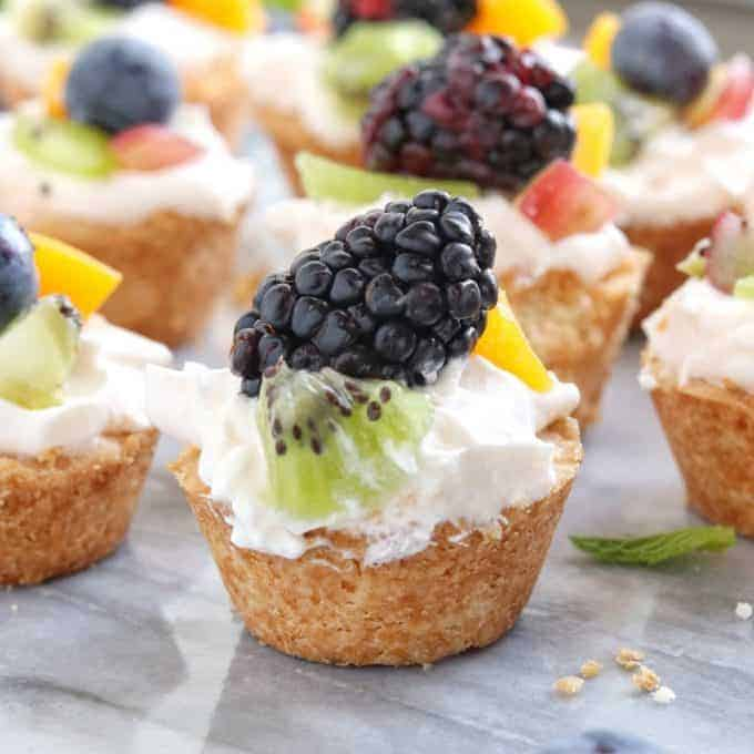 Mini Tarts a mini fruit tart recipe shown on white marble with a fresh blackberry on top with kiwi and peach.