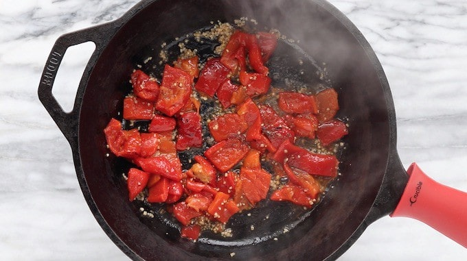 A tuna pasta recipe being made in a black cast iron skillet showing roasted peppers sauteed with garlic.