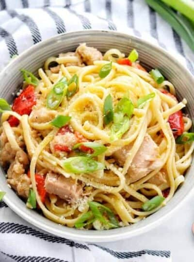 A bowl of pasta with tuna, peppers, and green onions.