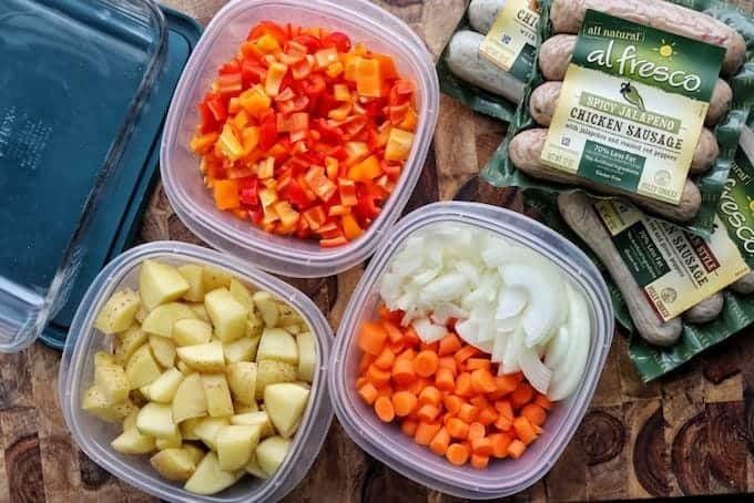 Meal prep ideas showing 3 Tupperware containers containing chopped peppers, potatoes, carrots and onions with chicken sausage packages next to them.