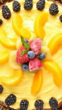 A fruit tart show with blackberries, peaches, and frozen strawberries.