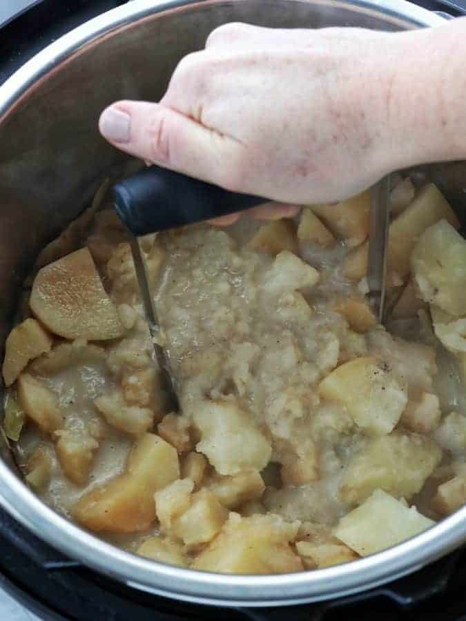 Irish potato and cabbage dish shown being made in an instant pot showing Irish potatoes cooked and being mashed.