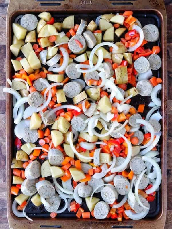 al fresco chicken sausage and veggies shown on a baking pan including potatoes, onions, peppers, and carrots.