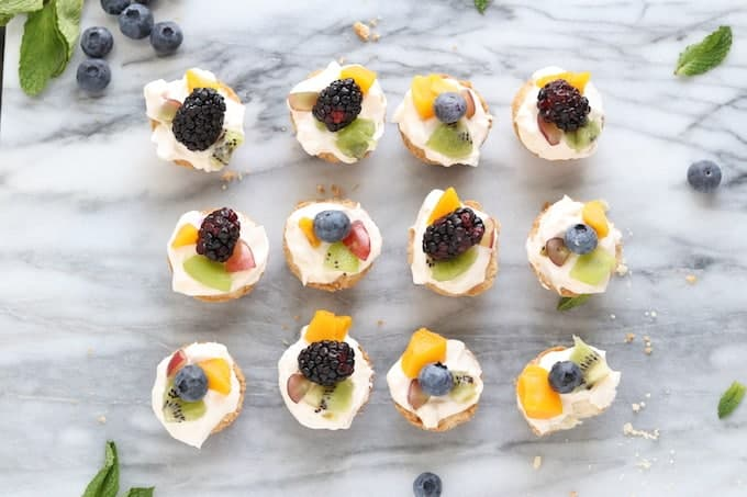 Summer fruit tart shown in 3 rows of 4 topped with fruit with mint and blueberries around the outside on white marble.