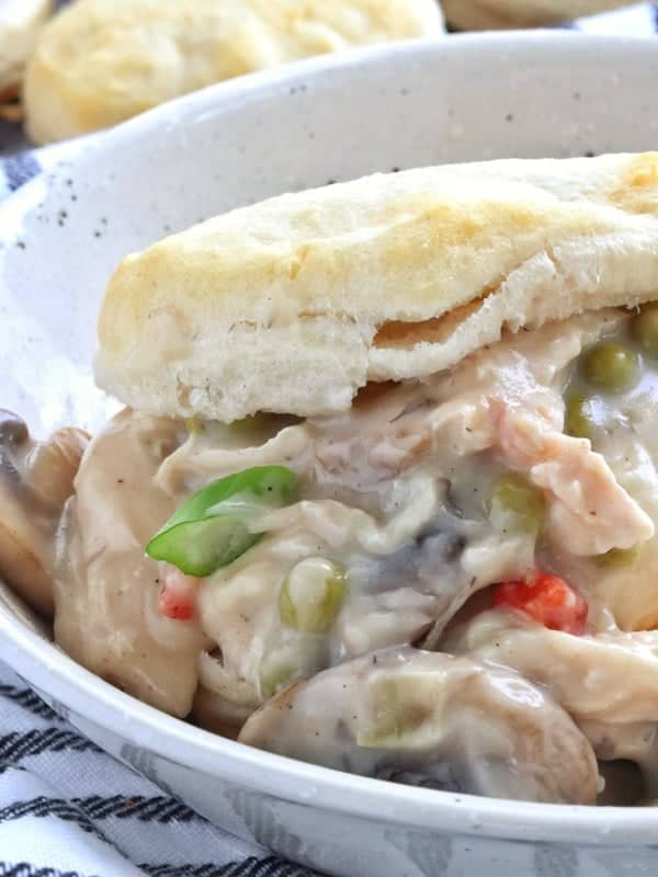 Easy chicken a la king with peas, mushrooms and a creamy sauce is shown close up in a white bowl on a biscuit