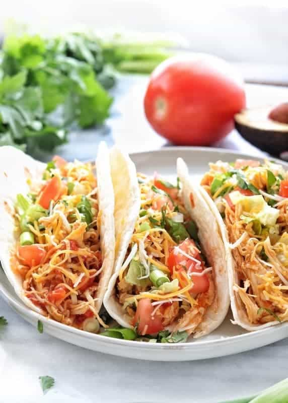 shredded chicken tacos instant pot showing three flour shredded chicken tacos on a white marble surface with cilantro and a tomato in the background