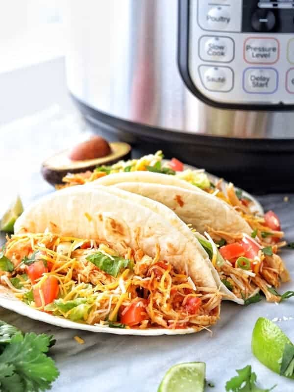 healthy shredded chicken tacos showing three flour shredded chicken tacos on a white marble surface with an instant pot in the background.