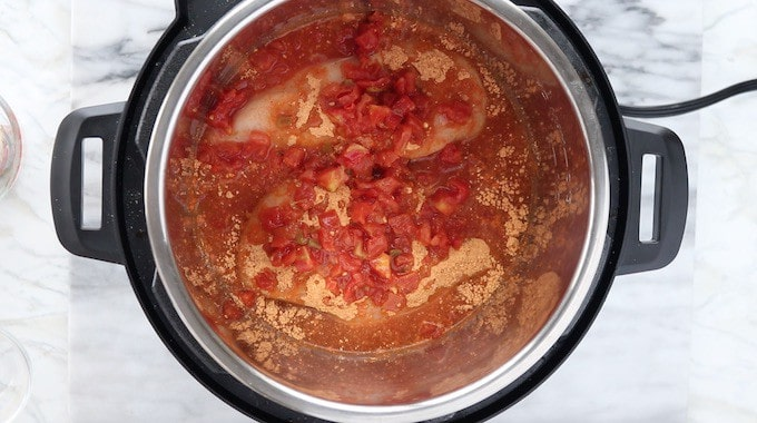 Instant pot Mexican chicken tacos being made in a pressure cooker showing raw chicken breast, tomatoes, taco seasoning and broth.