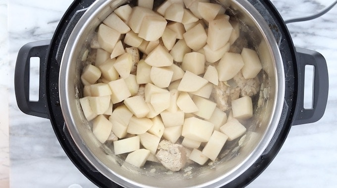 Instant pot chicken stew a pressure cooker soup recipe being made showing top down into instant pot showing diced potatoes.