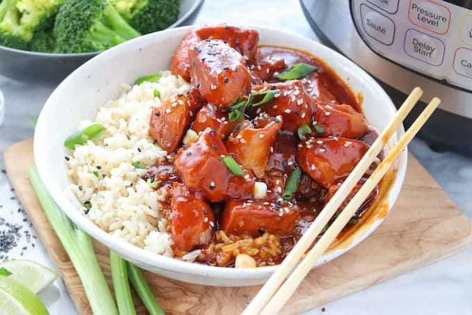 Chinese honey chicken, a pressure cooker chicken recipe shown on a bed of white rice in a white bowl with green onions and chopsticks next to an instant pot and a bowl of steamed broccoli all on a white surface with a wooden place mat under the pressure cooker chicken.