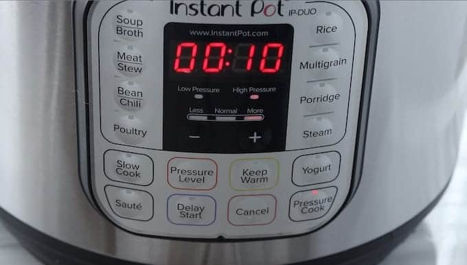 Instant pot chicken stew a pressure cooker soup recipe being made showing top down into instant pot showing 10 minutes of time on an instant pot.