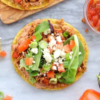 A tostada is loaded with refried beans, turkey taco meat, lettuce, tomatoes, and cheese.