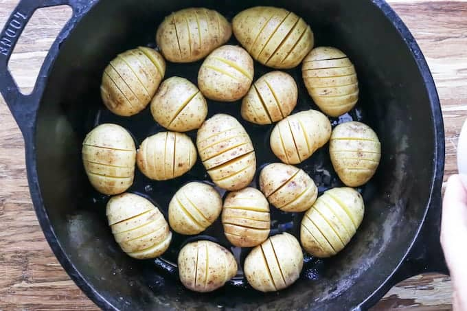 Hasselback potatoes with cheese being made in a black cast iron skillet showing the potatoes with slices on a wooden surface.