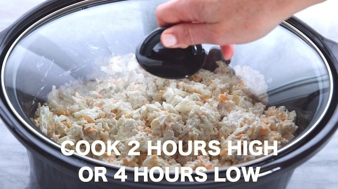 Crockpot Cheesy Potatoes, a cheesy potato recipe being shown in a black slow cooker with lid being placed on top of the crock pot all on a white and gray granite countertop with the words cook 2 hours high or 4 hours low written across the image.
