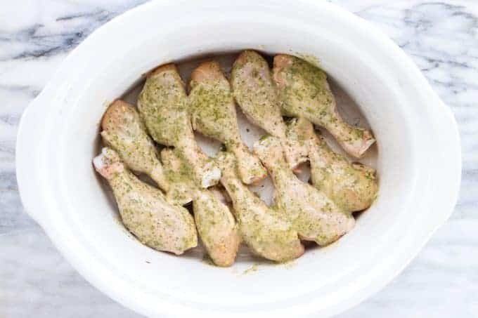 Crockpot Chicken Legs, a flavorful chicken recipe showing raw chicken legs with seasoning sprinkled on the top in a white slow cooker all on top of a white and gray granite countertop.