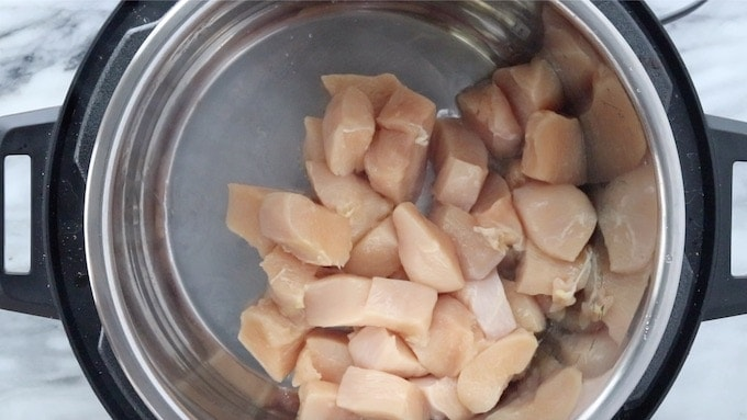 Chinese Honey Chicken showing bite-sized chicken pieces being cooked in the Instant Pot with hot oil.