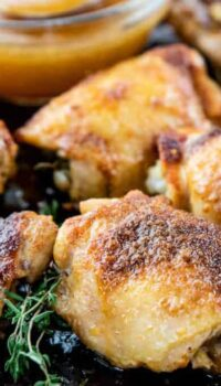 Cooked chicken thighs are shown on a baking sheet after broiling.