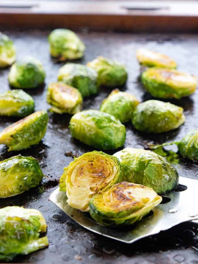 Baked Brussels sprouts, an oven roasted vegetable recipe being shown on a black baking sheet with a metal spatula